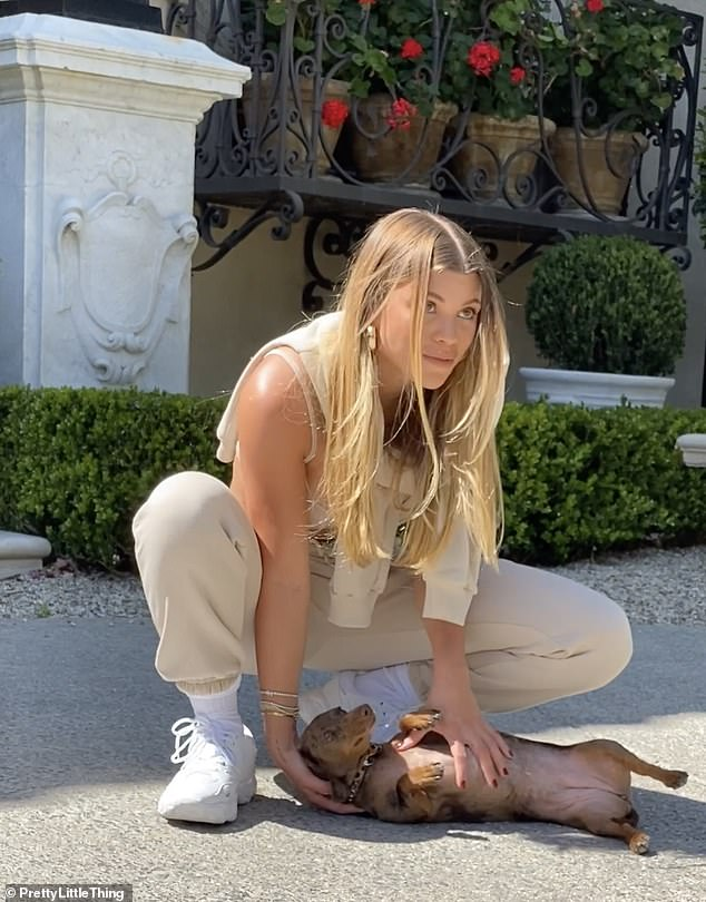 Sofia Richie plays with pet dog Hersh as she relaxes outside dad Lionel's LA mansion in behind-the-scenes look at her latest fashion shoot